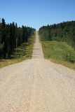 Long Way. A rural gravel road stretching through the Alberta foothills Royalty Free Stock Image