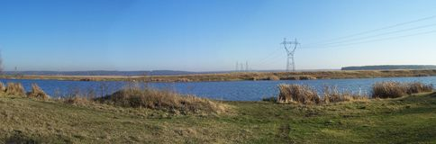 A long way. Panoramic country waterscape in autumn with two banks and long wires Stock Photo