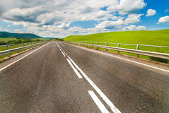 Long way between green fields with blue sky Royalty Free Stock Photography