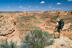 Long way to Go. A hiker pauses to peer into a remote desert canyon Royalty Free Stock Images