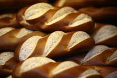 Long wheat loaves. Closeup many fresh baked whole long loaves wheat bread with crunchy crusts arranged in pile on seamless background, horizontal picture royalty free stock image