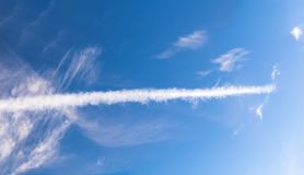 Long white condensation trail, on blue sky. Long white condensation trail, on blue sky background Royalty Free Stock Images