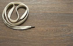 A long white cord on wooden dark background. Royalty Free Stock Images