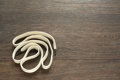 A long white cord on wooden dark background. Royalty Free Stock Photography