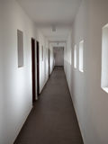 Long White Corridor.White Exhibition Hall. Technical Corridor In Large Building.Emergency exit.Corridor Exit Lighting.White Corridor With Empty Wall royalty free stock photography
