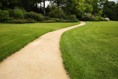 Long white curved garden path surrounded by lush foliage Stock Photo