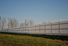 Long white fence. Image of a white fence bathing in the sun Royalty Free Stock Photo