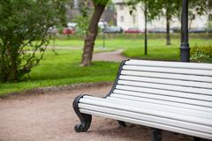 Long white painted wooden bench in summer urban park, nobody. Long white painted wooden bench is in summer urban park, nobody Stock Images