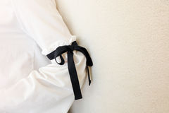 Long white sleeve with black string bow tie style details. Close up trendy fashion. Stock Photography
