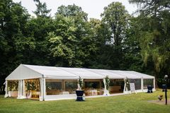 Long white tent for wedding party in the woods Stock Image