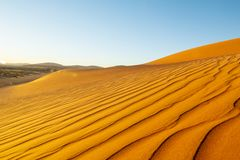 Long wind formed ripples with shadow defined edges in dunes of H. Long wind formed ripples with lens flare and shadow defined edges in dunes of Hidden Vlei Royalty Free Stock Image