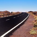 Long winding curve in an black empty road Stock Image
