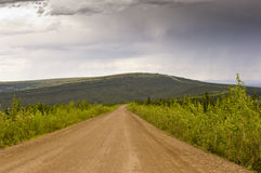 The long winding muddy Dempster Highway. The long winding muddy gravel Dempster Highway winds endlessly over hills in the Yukon, Canada Royalty Free Stock Images