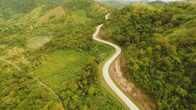 A long and winding road passing through green hills. Busuanga island. Coron. Aerial view. Philippines. A long and winding road passing through green hills stock video