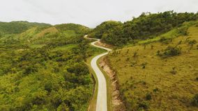 A long and winding road passing through green hills. Busuanga island. Coron. Aerial view. Philippines. stock footage