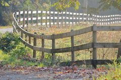 Long and Winding Wooden Fence Line. A long winding wooden fence line on a rural property border in the morning sunlight royalty free stock image