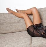Long Woman legs in stockings on sofa. Sexy women legs on sofa Stock Photos