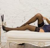 Long woman legs in stockings on sofa. Long sexy woman legs in stockings on white sofa Stock Photo