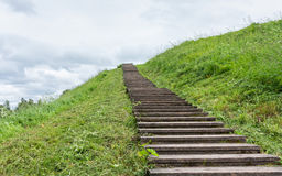 Long wood stairs to top of grass-covered earth-deposit. Belozersk, Vologodsky region, Russia Stock Image