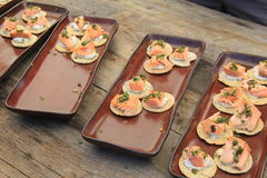 Long wood table with several brown trays offering appetizers of crackers topped with salmon Stock Images