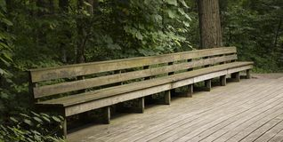 WOODEN BENCH ON WOOD WALKWAY. A long wooden bench beckons weary hikers to sit and take a rest as they watch nature unfold before them royalty free stock image