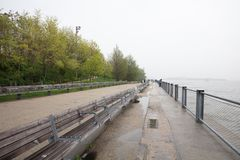 Long wooden bench, wet and empty after the rain, green grass and trees at Hadson river Manhattan New York. Hadson river Manhattan New York. Long wooden bench stock image