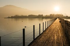 Long wooden boardwalk pier over water in golden evening light with a mountain landscape and people walking silhouette in the backg royalty free stock images