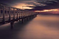 Long wooden bridge on the beach Stock Photos