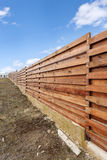 Long wooden cedar fence against blue sky. Royalty Free Stock Images