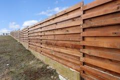 Long wooden cedar fence against blue sky. Stock Photos