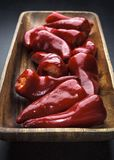 Long wooden dish of red peppers stock photo