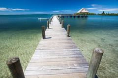 Long wooden dock with boat and  gazebo at end extends out into shallow waters of Caribbean cove Stock Image