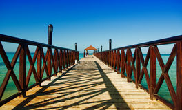 Long wooden dock with fence, stretching into the sea Stock Photos