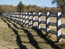 Long wooden fence. Picturesque wooden fence and shadow divide a pasture Royalty Free Stock Photography