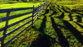 Long Wooden fence and shadow. Long wooden fence and its shadows separating two hillside hay fields stock images