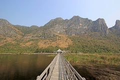 Long wooden jetty on nature lake. With mountain and nice sky background Stock Photos