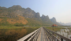 Long wooden jetty on nature lake. With mountain and nice sky background Stock Photo