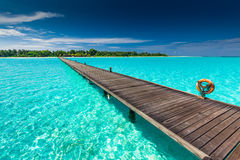 Long wooden jetty over atoll and a tropical island in Maldives Royalty Free Stock Photography