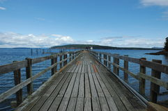 Long Wooden Pier. A long wooden pier juts out into the blue water on a bright day.  Orcas Island, Seattle Washington.  Open sky for text Stock Images