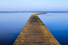 Long wooden pier on blue sea Royalty Free Stock Image
