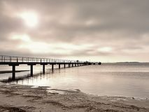 Long wooden pier at coast, cold morning, peaceful silent day Stock Images