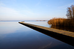 Long wooden pier over lake Stock Images