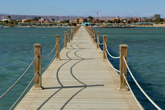 Long wooden pier into the sea. Royalty Free Stock Photo