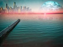Long wooden pier stretching into the ocean at beautiful sunset. Alien planet landscape - Long wooden pier stretching into the ocean at sunset with modern city stock image