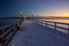Twilight walk on snow-covered pier, White Rock near Vancouver. The long wooden pier at White Rock, BC disappears into the distance while the last embers of a stock photography