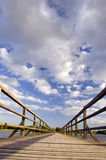 Long wooden plank bridge over lake and cloudy sky. Stock Photo