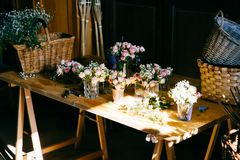 Long wooden table with different bouquetes of beautiful flowers. Pleasant smelling roses standing in glasses. Empty wooden backets royalty free stock images