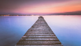 Long Wooden Wharf on Garda lake at sunset Royalty Free Stock Photos