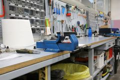 Long workbench in a mechanical workshop for repairs. Workbench in a mechanical workshop for repairs with blue heavy vice royalty free stock images