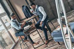 Long working day. Top view of young fashionable designer choosing fabric with his client while sitting in the workshop royalty free stock photography